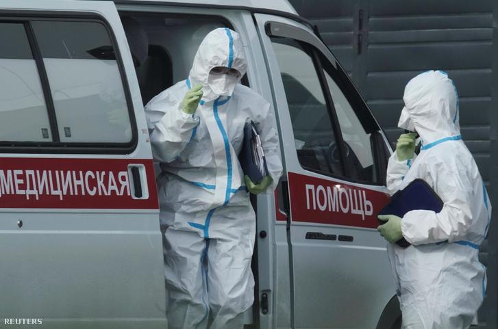 Egészségügyi specialisták védő öltözetben egy moszkvai koronavírusos betegekkel foglalkozó kórháznál 2020. április 21-én