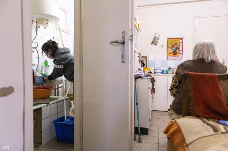 Önkormányzati közfoglalkoztatott a koronavírus-járvány miatt védőmaszkban takarít egy idős asszony otthonában 2020. március 25-én.