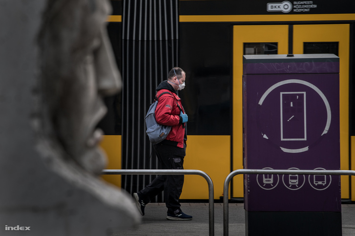 Maszkot viselő utas egy budapesti villamosmegállóban
