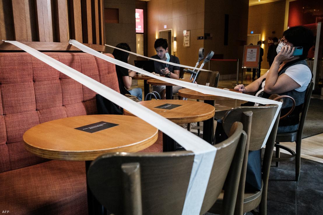Maszkot viselő, egymástól távolságot tartó emberek egy hongkongi kávézóban 2020. április 21-én. Hongkonban lazítottak a járványhoz kapcsolódó intézkedéseken, de többek között a távolságtartásra vonatkozó szabályokat május 7-ig fenntartják.
