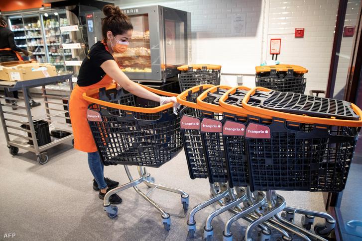 Alkalmazott fertőtleníti a bevásárlókocsikat egy párizsi szupermarketben 2020. április 8-án