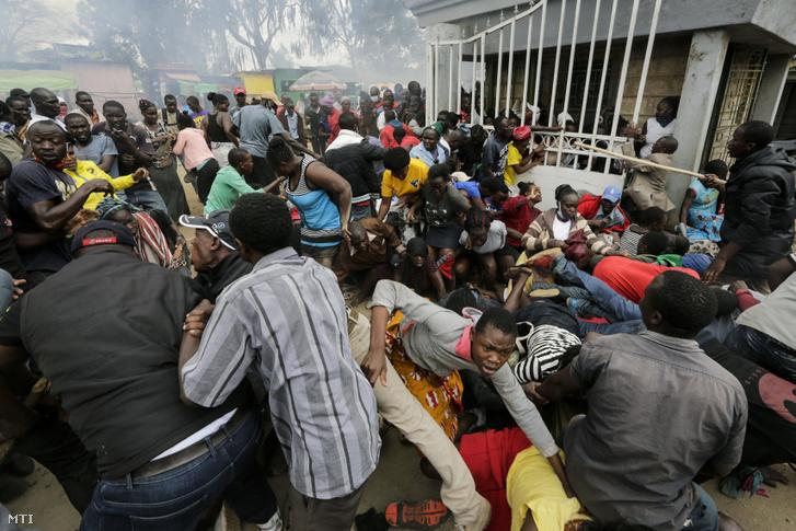 A koronavírus-járvány elleni védekezésül bevezetett korlátozó intézkedések miatt nehéz helyzetbe került emberek a tervezett élelmiszersegély-osztásra várva benyomulnak egy iroda területére a kenyai főváros, Nairobi szegénynegyedében, Kiberában 2020. április 10-én