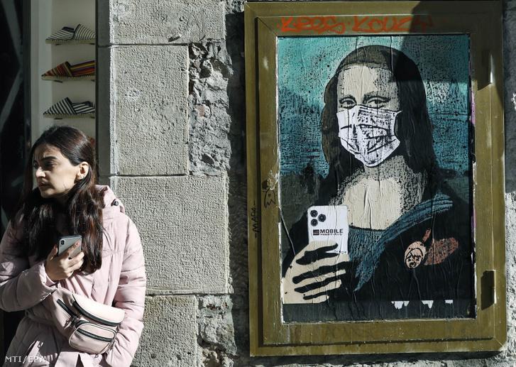 A TVBoy nevű utcaművész alkotása amely Leonardo Da Vinci híres Mona Lisáját ábrázolja arcmaszkban és egy mobiltelefonnal a kezében Barcelonában