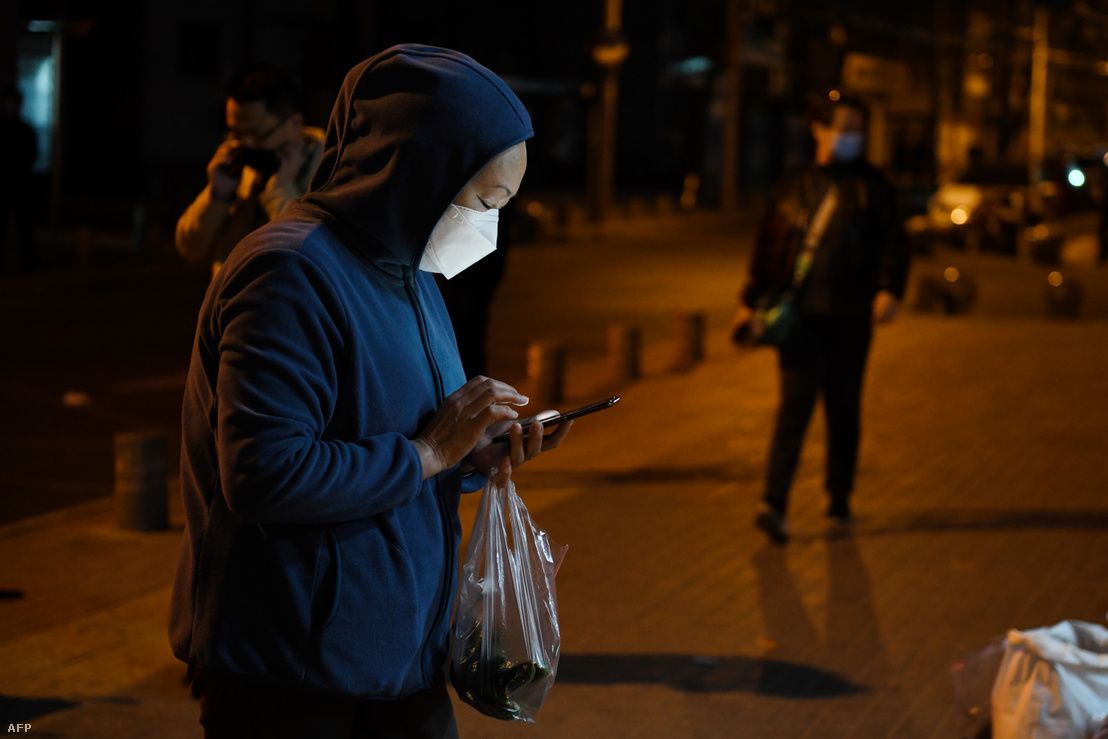 """Egy nő készül """"érintésmentes"""" fizetésre a mobiljával egy pekingi zöldségpiacon 2020. március 23-án"""