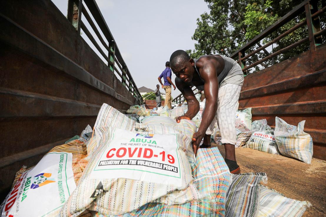 Egy férfi rizzsel tölt meg egy zsákot, a koronavírus-járvány miatt kiadott élelmiszersegélyekhez Abujában, Nigériában 2020. április 17-én