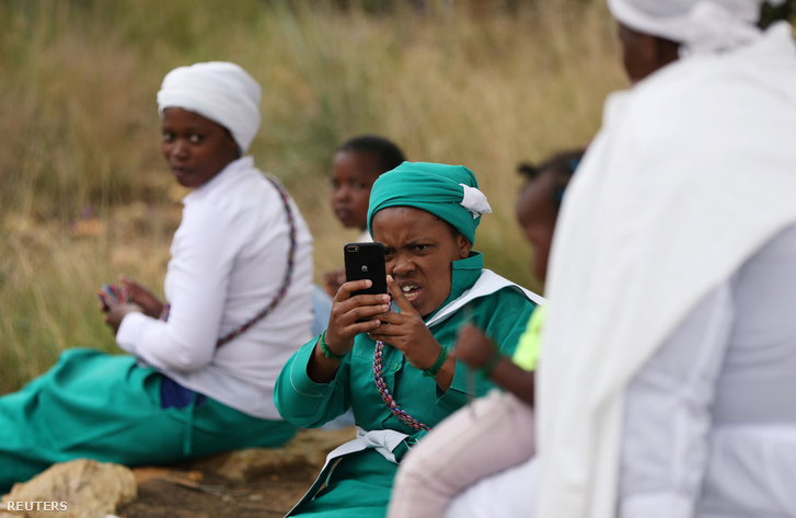 Egy afrikai keresztény gyülekezet tagja tartja kezében telefonját imádkozás után Sowetóban 2020. április 10-én