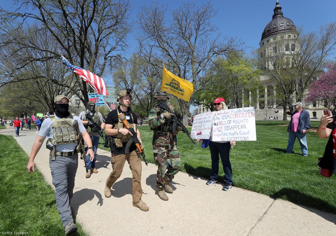 Fegyveres tüntetők követelik a korlátozások feloldását egy tüntetésen Kansasben 2020. április 23-án.