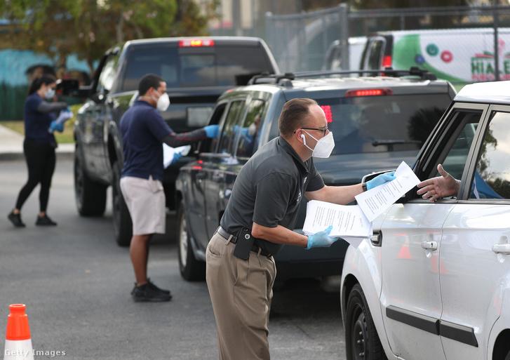 Önkormányzati dolgozók munkanélküli regisztrációs nyomtatványokat osztanak az arra váróknak egy floridai kisvárosban 2020. április 8-án.