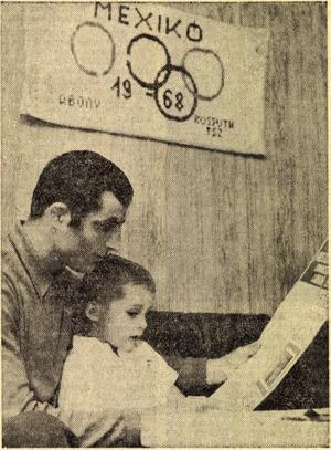 Varga János és kisfia Edmonton világbajnoki diplomáját vizsgálgatja. a falon pedig a szülőföld üzenete: abonyi faliszönyeg — az olimpiai aranyért. Forrás: Népsport 1972. július / Arcanum adatbázis