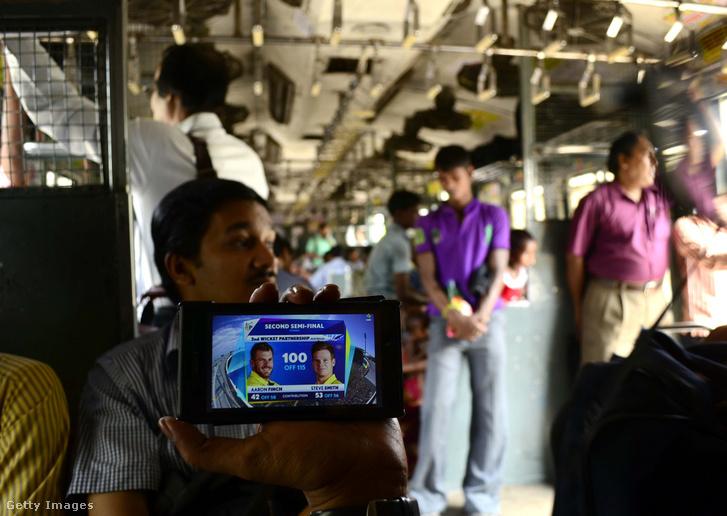 Egy vonat utasa sportmeccset néz munkába menet Kolkatában