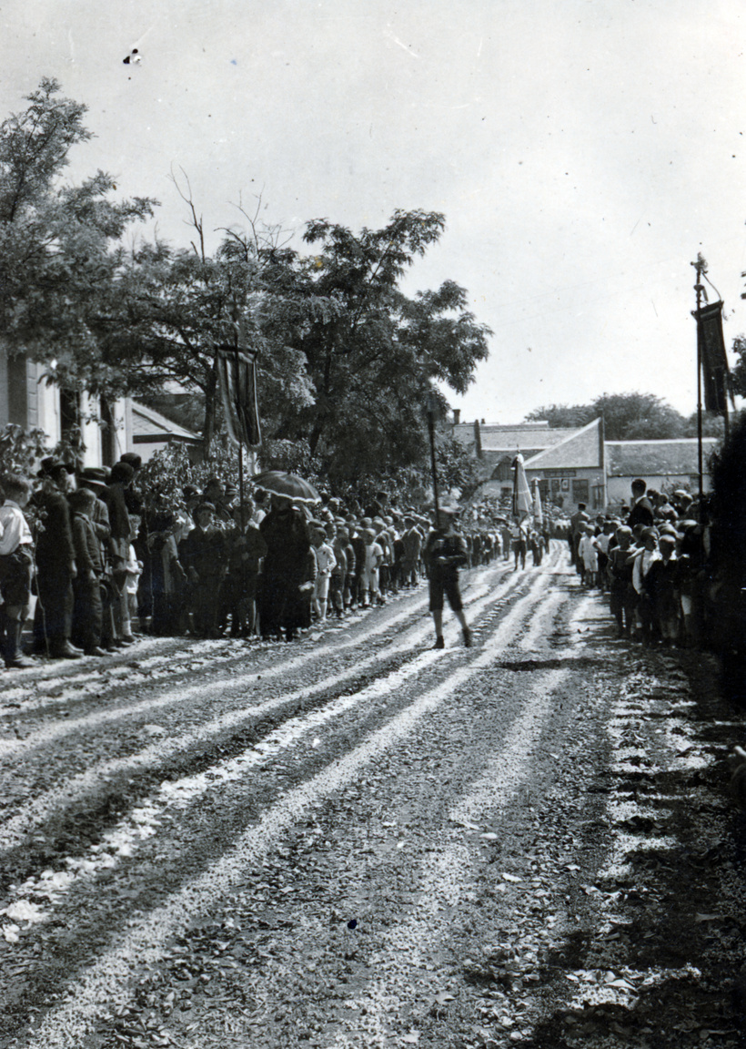 1930 – ÚrnapjaBudaörs (Wudersch) sváb falu volt, gazdag, konzervatív és nagyon katolikus. HÉV-vel lehetett innen bejárni Budapestre, Albertfalván át, a Fehérvári úton a Gellért térig (az én időmben már csak a Móricz Zsigmond körtérig). Kevés község mondhatta el magáról, hogy HÉV jár benne, hogy van kellő forgalom, élénk a termelés, polgárosodnak. Úrnapi körmenet zajlik éppen, útvonalát virágszőnyeggel hintették fel, nagyon katolikus dolog. Az Úrnapja (Fronleichnam) gyerekkoromban mindig csütörtökre esett, pünkösd után tíz nappal, a lényege a körmenet volt. A monstranciát (a felszentelt ostyát tartó, lángoló Nap-szerű foglalatot) föltartva vonult végig a pap a templomot körülvevő utcákon – ez valahogy Rákosi alatt se volt tilos. Persze mindenki maga dönthette el, hogy kíván-e vonulni, hiszen a besúgók nyilván jegyezték, ki van ott (ha nem maga a pap volt a besúgó, mert ilyen is volt sajnos). Képünkön azonban ez még nem probléma. A közönség (miért főleg nők?) nagyon várják már a Szent Testet, de csak egy gyerek (vagy alacsony ember) közeledik, talán zászlóval. Manapság az Úrnapját – mivel csak Ausztriában munkaszünet – nem csütörtökön, hanem a rá következő vasárnap tartják, hogy mindenki ráérjen.