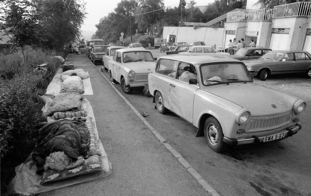 1989 –TürelemjátékRengeteg minden történt az 1989-es évben. Kádár meghalt, Nagy Imrééket újratemették, megszűnt az MSZMP, Szűrös Mátyás (emlékszik rá valaki?) kikiáltotta a köztársaságot. Nekem mégis az NDK-sok migrációja a legmaradandóbb emlék. Hogy már senki se akart erőszakot alkalmazni velük szemben, de a magyar hatóságok eleinte azért még segíteni sem akarták őket. A keletnémetek, akik Magyarországon vagy messzebb, a számukra engedélyezett országokban: Romániában és Bulgáriában nyaraltak, egyszerűen nem voltak hajlandók visszamenni az NDK-ba, hanem azt követelték, hogy engedjék őket Ausztrián át Nyugat-Németországba (az NSZK-ba). Letáboroztak Magyarországon és várták, hogy mi lesz. A képen a budai Nógrádi utca látható, ahol a nyugatnémet nagykövetség konzuli osztálya működött, mely elvileg jogosult volt útleveleket, vízumokat kiadni – a saját állampolgárainak. Erre várnak az itt tanyázók. Trabantjukon NDK rendszám, kemping- és strandcikkeken alszanak. Az egyik garázsban valaki büfét nyitott, hiszen ennyi embert etetni, itatni kell. Aztán Horn Gyula külügyminiszter közölte, hogy vége az egész vasfüggönynek, menjenek. És átvágta a drótot.