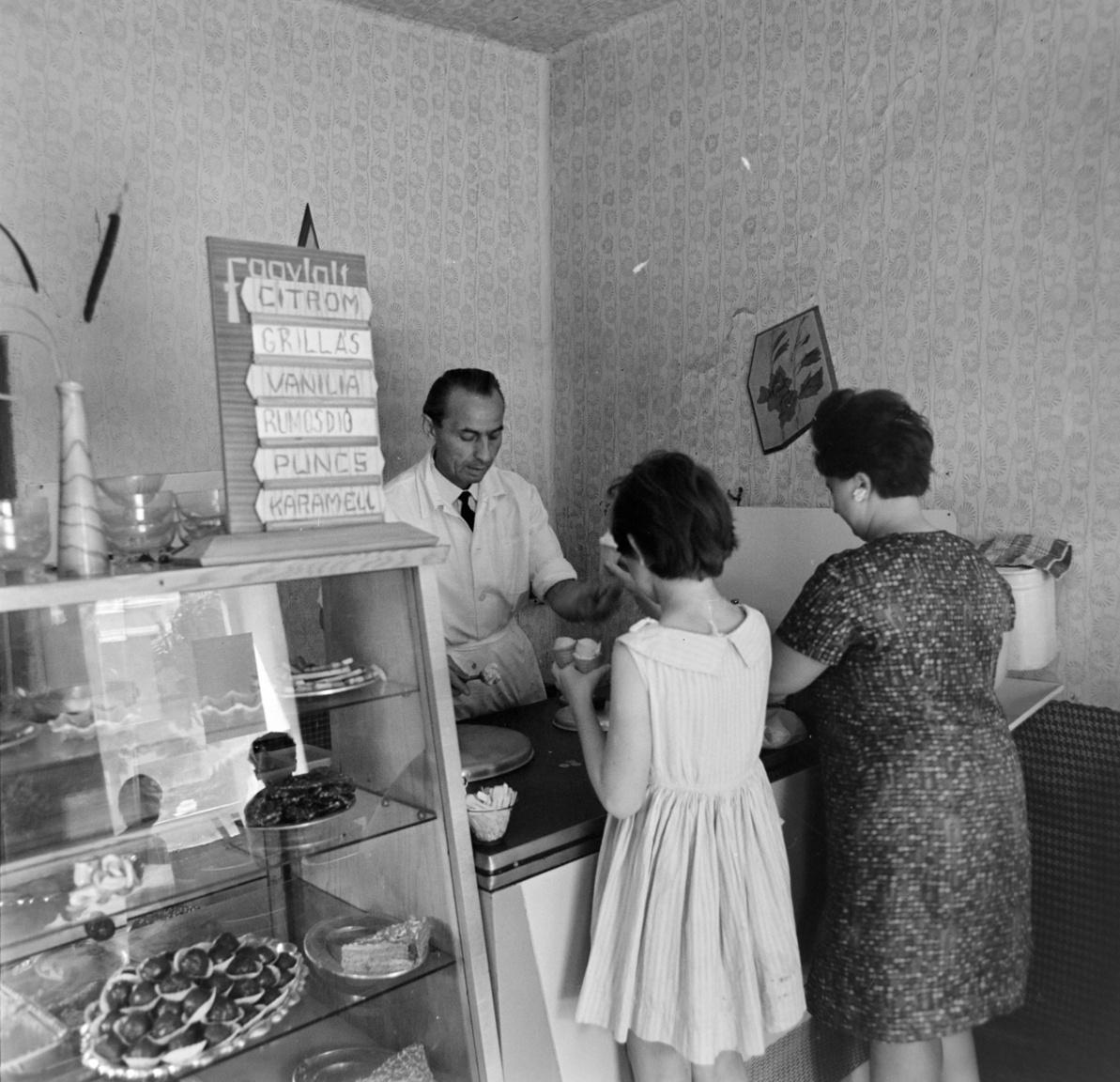 """1968 – CukrászdaOrosházán vagyunk, egy cukrászdában. Kicsike az üzlet, ez abból látszik, hogy a kézmosási lehetőséget csak nagy ügyeskedés árán sikerült beszorítani a pult mellé: a víztartály alján csap, alatta pedig tálca a piszkos víz felfogására. Ez csak a KÖJÁL (= Közegészségügyi és Járványügyi Állomás) előírásainak betartása miatt kellett, nyilván ragaszkodtak hozzá, hogy ahol élelmiszer-fogyasztás történik, ott kézmosási lehetőségnek kell lennie. (És vajon vécé volt?) A fagylaltkínálat mai szemmel nézve bizony egyoldalú, nincsen semmilyen gyümölcsös (a citromosat nem lehet annak nevezni), a felsorolt fagylaltok ugyanannak a tejszínes alapnak különböző ízesítései. Ettől még finomak lehettek, én a rumosdiót választottam volna. A """"grillás"""" szónak """"s""""-sel való írása általános volt (ahogy a """"masszás"""" szónak is, bár a franciás """"grillázs"""", """"masszázs"""" helyesebbnek számított). A víztartály tetején csíkos kéztörlő."""