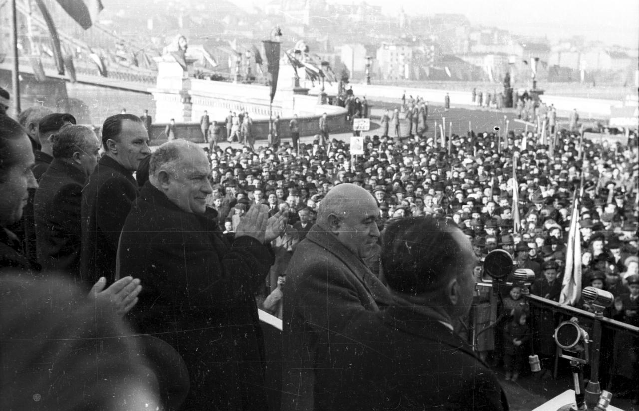 1949 – HídavatásÚjjáépült a németek által felrobbantott Lánchíd, négy évvel a tönkretétele után. Ekkor már totális szovjet típusú kommunista diktatúra volt Magyarországon, az avatóünnepségen a diktátor, Rákosi Mátyás mondott beszédet. Ö a kép közepén az alacsony, kopasz férfi, a Magyar Dolgozók Pártja főtitkára. Ravasz és ügyes politikus volt, és mivel Moszkva (azaz Sztálin) bizalmát élvezte, bármit megtehetett. Tőle balra egy jelentéktelenebb figura, Bebrits Lajos közlekedésügyi miniszter (1956 után stockholmi nagykövet – tény, hogy jól tudott angolul). Tőle balra alig látható egy alacsony fekete hajú (sapkájú?) személy, a következő pedig Kádár János belügyminiszter, akit Rákosi két év múlva koholt vádakkal bebörtönöztetett. Életfogytiglanra ítélték, majd másfél év múlva szabadon engedték és minden tisztségébe visszahelyezték. Kádár elődje a belügyminiszteri székben Rajk László volt, de ő ezen az ünnepségen nem lehetett jelen, ugyanis egy hónappal korábban koholt vádak alapján felakasztották. De a Lánchíd valóban újjáépült, és – ellentétben a Rákosi-rendszerrel – ma is áll. A diktatúrák kevésbé tartósak, mint a lánchidak.