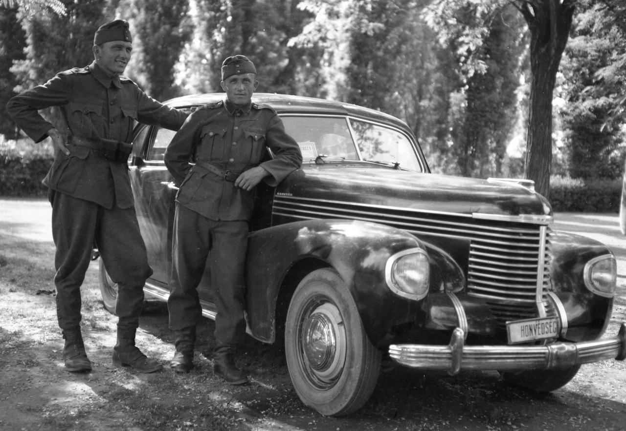 """1941 – BúcsúpózVégre, Magyarország is belépett a háborúba, 1941. június 27-én a szovjeteknek átadott hadüzenettel. Hogy mi baja volt a magyar kormánynak a Szovjetunióval? Csak az, hogy szövetségesünk, a Német Birodalom megtámadta őket, így hát nekünk is muszáj volt.De azért nyár van, és egy klassz modern autónak nagyon lehet örülni. Ezt bizony elrekvirálták valakitől, ne furikázzon a saját szakállára az állampolgár (pláne, ha netántán zsidó!), majd inkább furikázunk mi. Ekkoriban az autók még eléggé megbízhatatlanok voltak, a jó sofőrnek ajánlatos volt szerelői tudással is rendelkeznie, a gyakori kerékcserékről nem is beszélve. (Még én is cseréltem kereket fiatalon, elég természetes dolog volt – ma már úgy hangzik, mintha azt mondanám: a lovammal átgázoltam egy megáradt patakon.) A rendszámot lecserélték """"Honvédség"""" táblára: no de rendszám ez? Vagy ez most a """"Frissen lefoglalt járműveink"""" című kiállítás?"""