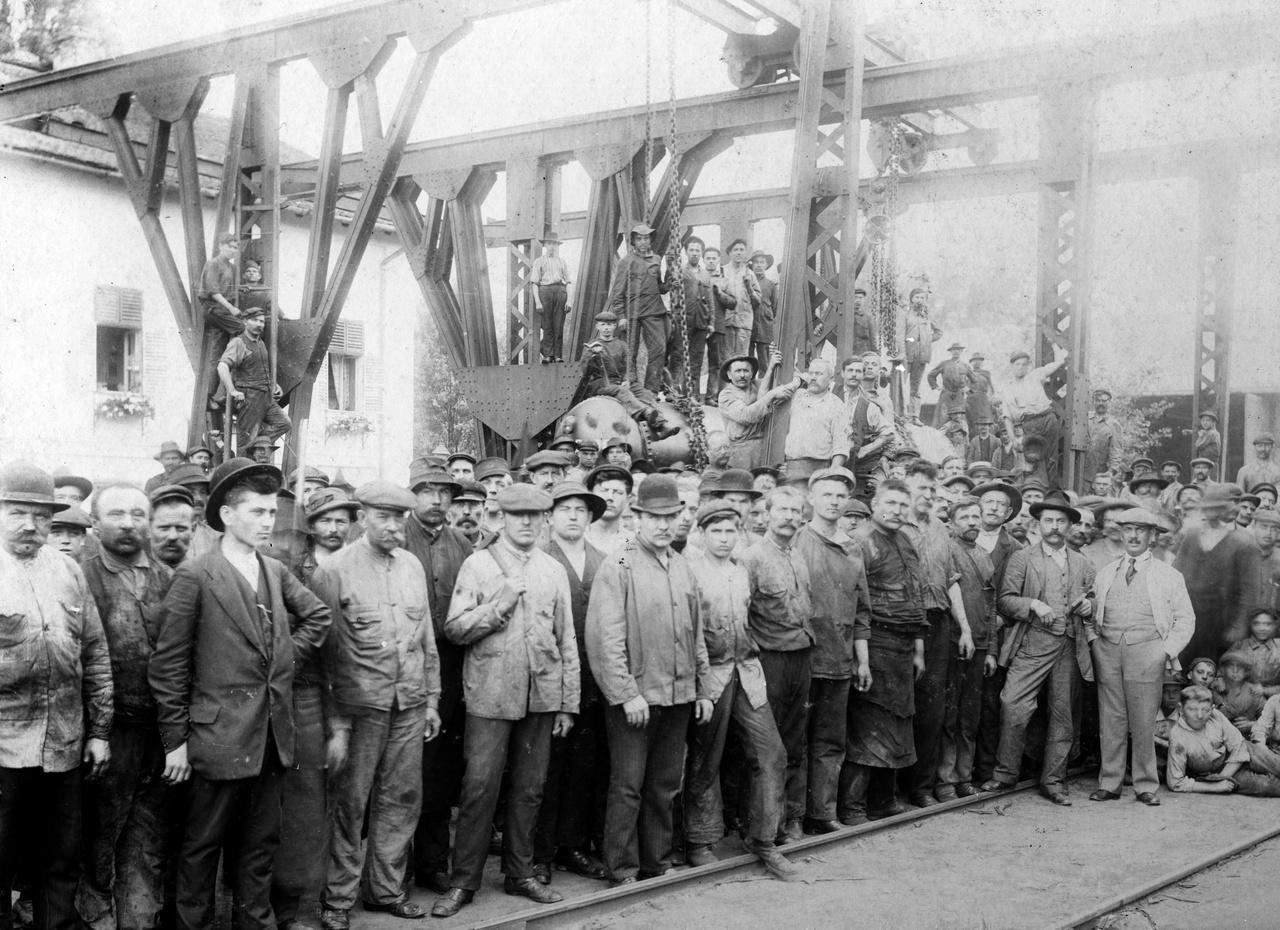 """1902 – MunkásgyűlésEzeknek a hajógyári munkásoknak, úgy látszik, nem mondta a fényképész, hogy """"Barátságos arcot kérek"""", nyilván nem is akartak barátságosnak látszani. Talán szakszervezeti megmozdulás, talán sztrájkra készülnek – ekkor már erősödőben volt a munkásmozgalom. A jobb szélen gyerkőcök, ők persze vidámabbak: könyököl a legelső a földön, mint majd teszi tizenvalahány év múlva a hazaküldött katonafotókon. A gyerekek előtt áll egy világos ruhás, köpcösebb férfi zsebre dugott kézzel: ő lehet a gyáregység vezetője (vagy a tulajdonos?), aki az iménti beszédében megpróbálta csitítani a munkásokat. A legérdekesebb a baloldalt elöl álló sötét ruhás fiatalember, feltolt keménykalapban. Ő a szakszervezeti vezető, később majd illegális kommunista lesz, ha megölik, utcát és laktanyát fognak elnevezni róla. Nyilván derék, szimpatikus ember, de az ilyeneknek az emlékét úgy összenyálazták később a pártpropagandisták, hogy csak lenéző ellenszenvvel tudtunk rájuk gondolni. Ha pedig életben marad, pártvezető lesz, ami kiöli belőle ezt a távolba néző, eltökélt, rokonszenves fiatalembert."""