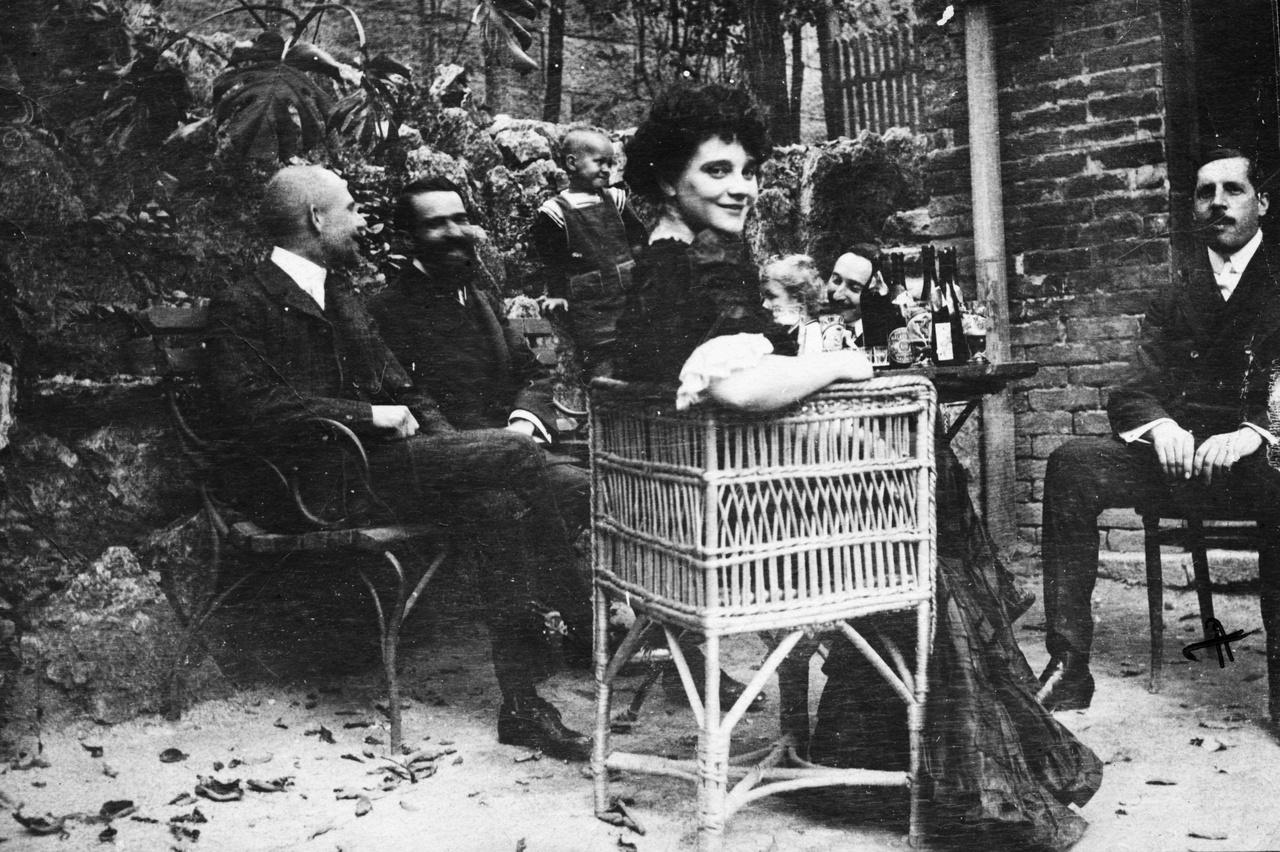 """1910 – PrimadonnaKellemes budai társaság, a középpontban Medgyaszay Vilma operettprimadonna, színésznő, sanzonénekesnő. Huszonöt éves és már országosan ismert. Szép hangja van, hozzá a kor ízlésének maximálisan megfelelő, jó húsú, szolid alkata (akkoriban a """"szolid"""" még azt jelentette: erőteljes, stabil, teherbíró). Ismertségét annak köszönhette, hogy pár évvel korábban a Kacsóh-Bakonyi-Heltai-féle János vitéz-operettben ő alakította Iluskát; partnere János vitéz szerepében Fedák Sári volt. (Akkoriban se mentek a szomszédba egy kis gender-pimaszságért!) Medgyaszay (közismert becenevén Mimi) láthatólag élvezi ezt a kerti délutánt, az urak társaságát, és lám, a borból is jócskán fogyott. Később komoly szerepet vállalt a progresszív zeneszerzők népszerűsítésében: Bartók, Kodály, Lajtha dalait és népdalfeldolgozásait adta elő, lemezre is énekelte. Mai füllel a népdalfeldolgozások – és Medgyaszay előadásmódja – mesterkéltnek tűnnek, de a maga korában missziót teljesített velük. Aradon született, Stand Vilmának hívták, a Medgyaszay az anyja neve volt. Akkoriban nem illett németes vagy szlovákos hangzású névvel színpadra lépni. Rejtély, hogy ezt Fedák hogy úszhatta meg."""