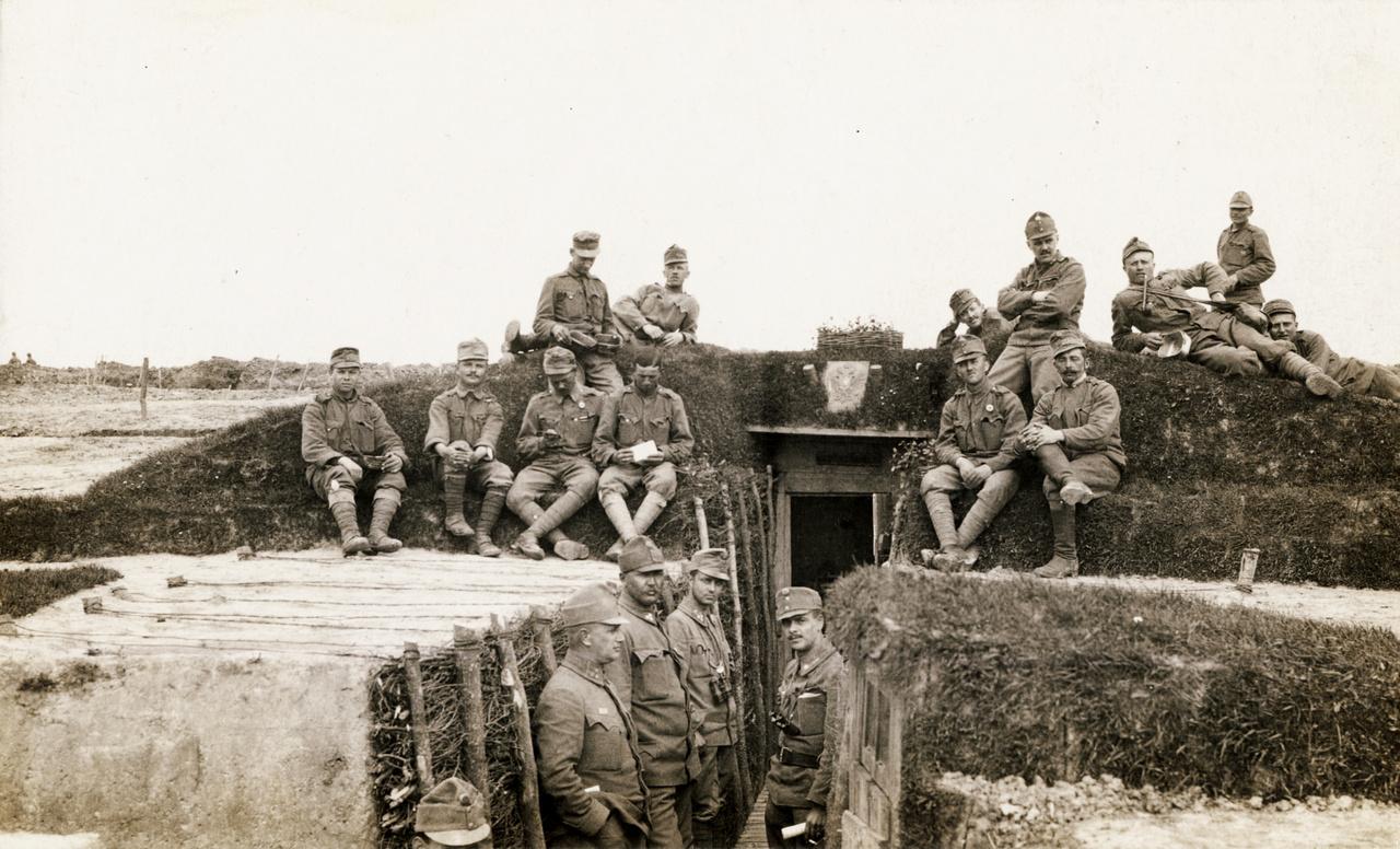 """1915 – LövészárokZajlik a Nagy Háború, de ez még nem a rémes része. Lám, milyen takaros kis lövészárkot csináltak a fiúk! Elégedettek is a munkájukkal, tűrik az okvetetlenkedő fényképészt. Fönt a dombocskán a jellegzetes könyöklő """"katonafotós"""" tartást látjuk, méghozzá automatikusan a kép középvonalára szimmetrikusan könyökölnek a bal, illetve jobb könyökükre. A lejjebb ülők közül az egyik nem figyel, sapka sincs rajta, ejnye, fiam! Levelet olvas, persze, a menyasszonyától vagy az ifjú feleségétől – pedig úgy látszik, nemrég vannak még kint a fronton, lesz ez még ígyebb is. A mellette ülő társa meg mobilozik – oppardon, nem mobilozik, mert ekkor még nem volt mobil. De akkor mit csinál, hiszen az egész test- és kéztartása olyan? A zsebóráját vizsgálgatja elmélyülten?"""