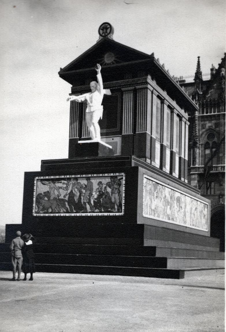 """1919 – DíszletA háborúnak vége, de a zűrzavarnak nem – sőt az csak most kezdődik. Nincs már Nagy-Magyarország, de van kommunista terror - más néven Tanácsköztársaság amely egy csapásra mindent meg akar változtatni. El kell ismerni, ezt néha színvonalasan csinálták, mint ez esetben. Ez az építmény - valójában egy nagy doboz – az Országház mellett áll, a Kossuth Lajos téren (melyet átkereszteltek Köztársaság térre, ugyanis a későbbi Köztársaság, mégkésőbb II. János Pál pápa tér neve ekkor még Gróf Tisza Kálmán tér). Itt áll, és fő célja az, hogy eltakarja gróf Andrássy Gyula lovas szobrát a május 1-jei felvonulás idejére. Ezt nézzék a felvonulók, ne Andrássyt! Az építmény a maga nemében kiváló, szépek és a kor színvonalán állnak az oldalfalak képei. A főalak, a fehér munkásszobor gyenge, de ne legyünk telhetetlenek: ekkora szobrot nem könnyű ilyen rövid idő alatt csinálni. A kulissza neve """"Munka Háza"""". Nem tudom, meddig kellett Andrássynak és a lovának bent fuldokolnia, legföljebb pár hónapig, aztán jött az újabb rendszerváltás, a román megszállásról nem is beszélve."""