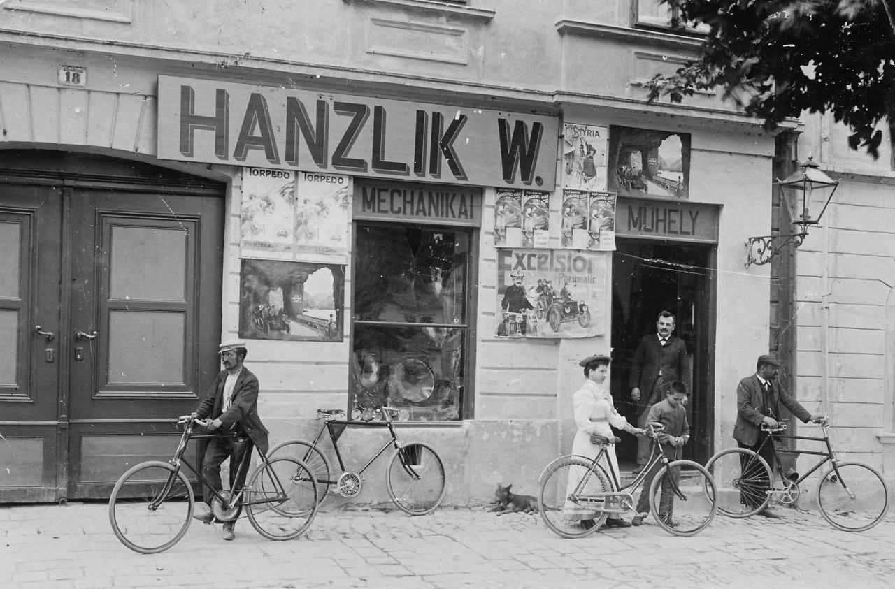 """1913 – VasparipaAz ajtóban, gondolom, maga Hanzlik úr áll, a tulajdonos, nézi, ahogyan a boldog vevők szanaszét hordják a frissen vásárolt kerékpárokat. De az is lehet, hogy csak beugrottak hozzá biciklin valami alkatrészért. Mindenesetre a nő kezében női vázas kerékpár van, míg a többi mind férfigép, szóval kicsit reklámízű a felvétel. Fájdalmas belegondolni, hogy egy ilyen kis helyen, mint Magyaróvár (mely csak 1939-ben egyesült Mosonnal) naprakész """"mechanikai műhely"""" létezett, amely az éppen forgalomba került nyugati dolgokat is forgalmazta, mint az a plakátokból kiderül. Hová zuhant mindez a második háború után! A műhely a Fő utca 18.-ban működött, Hanzlik úr német lehetett, erre keresztnevének """"W"""" betűjéből következtethetünk, de a vezetékneve olyan általános keletosztrák-nyugatmagyar-északhorvát-délszlovák, hogy azt a Jóisten se bogozza ki. Ha Bécsben élt volna, Hanslicknak írta volna, Pozsonyban meg Hanzlíknak. Testtartásán látszik a támogató jóindulat, mellyel kuncsaftjait szemléli. Isten áldja a tisztes ipart!"""