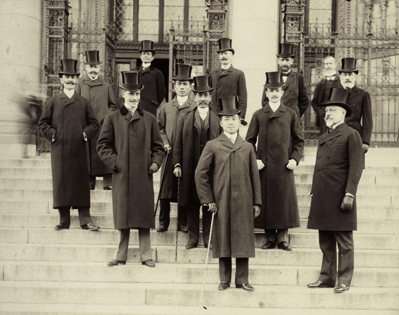1897 – Királyi turnéA képen elöl álló fiatalember nem más, mint Chulalongkorn sziámi király. Nem is olyan fiatal: 44 éves, ekkor tette első nagy európai körútját, Budapestre is ellátogatott. A buddhista vallásból következően számos nevet viselt, V. Ráma néven is nevezték. 57 évet élt (1853-1910), körülbelül száz felesége, ágyasa vagy élettársa volt, 77 gyermek maradt utána. Nyugati neveltetést is kapott, angolul-franciául jól tudott, fiai egy részét (33 fia volt) az angliai Eton magániskolájába járatta. Ő és kísérete – legalábbis az európai körutazás erejéig – annyira idomult az európai divathoz, etiketthez, hogy első látásra a sok cilinderes úr közül nem könnyű megállapítani: ki sziámi és ki magyar. Úgy tűnik: akinek fölfelé van pödörve a bajusza, az magyar, akinek nincsen, vagy lefelé konyul, az sziámi. Chulalongkorn jó uralkodó volt, sokat modernizált, és ügyes lavírozással elérte, hogy országa (ma Thaiföld) ne váljon gyarmattá. Gondolom, néhány feleséget is hozott magával, hiszen akkoriban egy európai körút hónapokig tartott, de a nőknek még nem volt szokás jelen lenni az ilyen formális alkalmakon. Vagy csak nem tudta eldönteni, melyiket hívja – inkább egyiket se hívta.