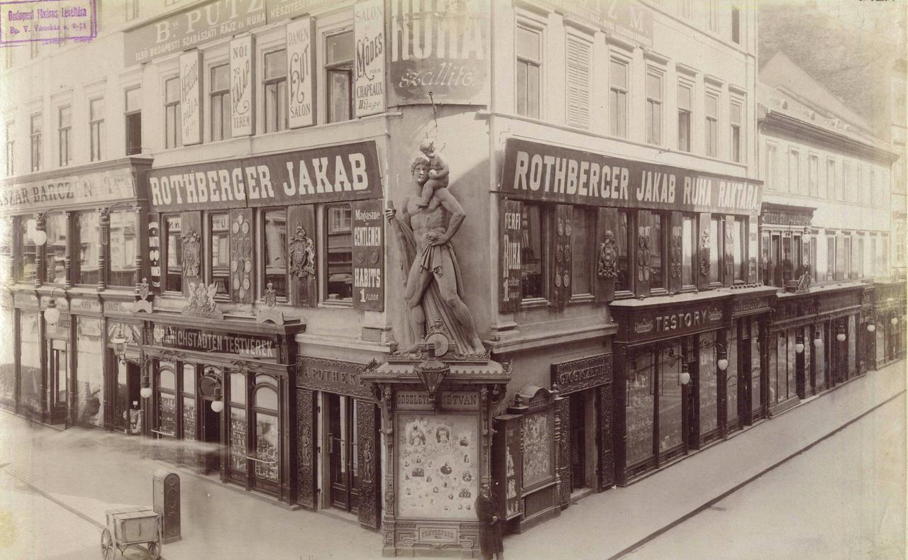 """1895 – KolosszusA pesti Váci utca és Kristóf tér sarkán állunk, ez akkoriban is drága és elegáns helynek számított. Még az emeleteken is működtek üzletek, így például Rothberger Jakab """"ruharaktára"""" (azaz készruha-üzlete), amely - a korban szokatlanul! - angolul is hirdeti magát. A szobortól balra ugyanis ez áll: """"Magasine / Gentlemen / Habits / 1 Floor"""", amiben a """"habits"""" rettentő régies, angolul már csak papi-apácai ruházatra használták, de hát az angol olyan távoli, és különben is: franciául így van, az angol pedig alapjában egy eltorzított francia, nemde? A boltosnevek mind más-más háttérre utalnak: Rothberger, Goszletics, Granichstädten, Putz, Testory – egy robbanásszerűen növekvő nagyváros olvasztótégelyében találkoznak. A szobor, amely a sarki patika cégéreként szolgált, meglepően modern: mintha jó 30-40 évvel későbbi lenne. A két háború között az olasz fasizmus művészete kedvelte az ilyen férfiaktokat. A terecske névadóját, Szent Kristófot ábrázolja, aki a legenda szerint hatalmas termetű ember volt. Egy kisgyermeket átvitt a megáradt folyón, mire a gyermek közölte: ő Jézus, és a szolgálatért a férfinek mennyei jutalomban lesz része.Attól kezdve a neve Christo-phoros, azaz """"Krisztus-vivő"""" lett. Keresztény hitéért a rómaiak kivégezték, s azóta ő az utazók, így például a kamionsofőrök védőszentje."""