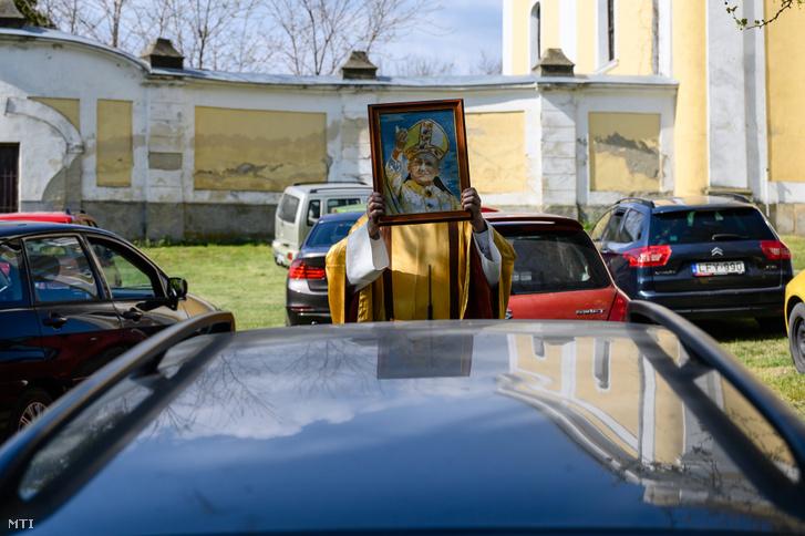 Ilyen kreatív megoldásra még szükség lesz Budapesten, vidéken már nem. Itt éppen Mihályi Miklós plébános Szent II. János Pál pápa szentképével kezében áldja meg az autójukban ülő híveket az előszállási Kisboldogasszony-templom előtt 2020. április 26-án