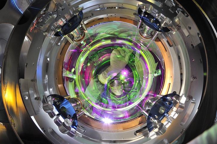 Infravörös közeli lézersugarat tükröző 42 kilogrammos tükör a Virgo detektorban, a fotó közepén egy kutató látható teljes védőfelszerelésben, ami az efféle érzékeny műszereknél amúgy is kötelező