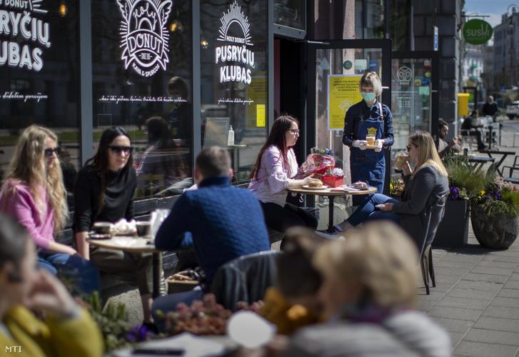 Védőmaszkot viselő pincérnő szolgálja ki egy vilniusi cukrászda vendégeit 2020. április 30-án. A litván kormány május 11-ig meghosszabbította a járvány miatt bevezetett korlátozó intézkedések hatályát de engedélyezte a múzeumok könyvtárak terasszal rendelkező kávézók fodrász- és kozmetikusüzletek továbbá a bevásárlóközpontokban működő boltok újranyitását.