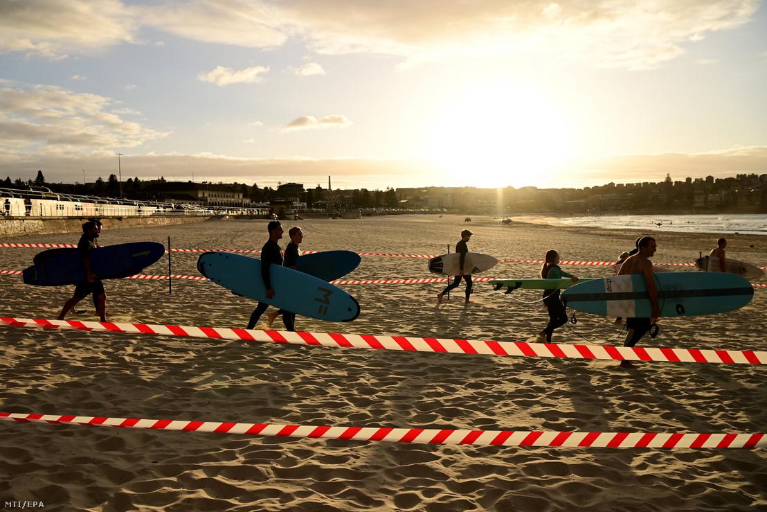 Szörfösök mennek a tengerbe miután újra megnyitották a Bondi Beach tengerparti strandot Sydney-ben 2020. április 28-án.
