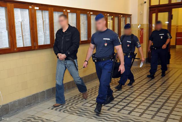 Bilincsben és vezetőszáron viszik a tárgyalóterembe Pesti Központi Kerületi Bíróságon a BRFK egyik rendőrtisztjét, akit 2012. május 31-én korrupció gyanújával vettek őrizetbe.
