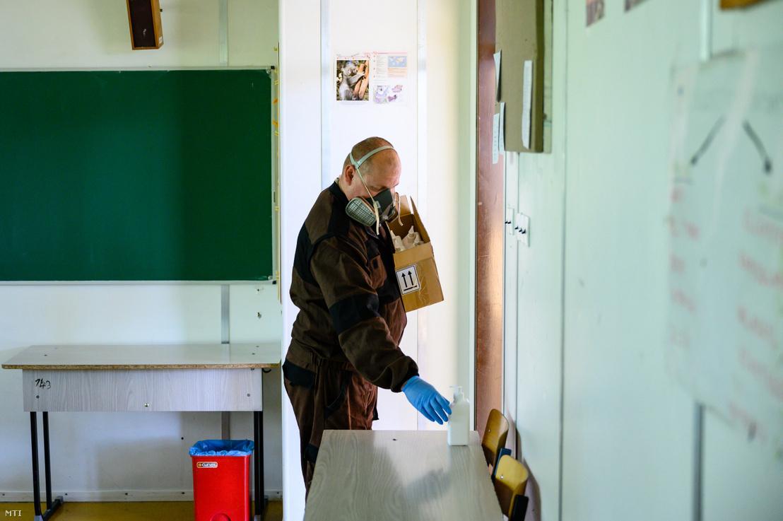 Kézfertőtlenítőt helyeznek ki a székesfehérvári Árpád Szakképző Iskola és Kollégium egyik tantermébe 2020. április 30-án.