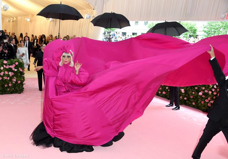 Először is ebben a hatalmas, rózsaszín estélyiben jelent meg, amit egy idő után segítői fellibbentettek róla