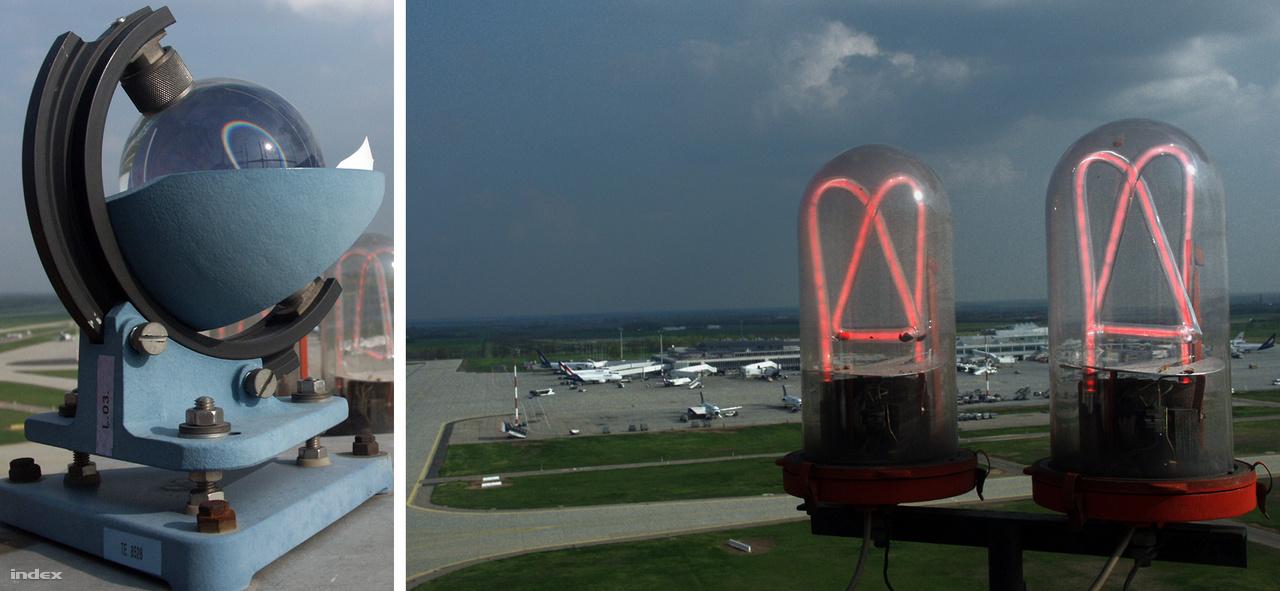 Az irányítótorony tetején: balra egy meteorológiai műszer, jobbra a éjszakai vörös irányfények, a háttérben a 2-es terminál.