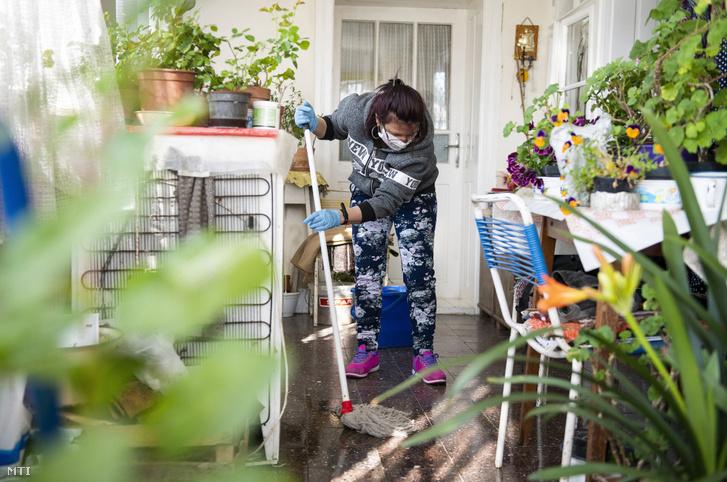 Ez is közmunka, koronavírus-járvány miatt védőmaszkban takarít az önkormányzat egyik közfoglalkoztatott házi segítségnyújtója egy idős hölgy otthonában Paszabon 2020. március 25-én