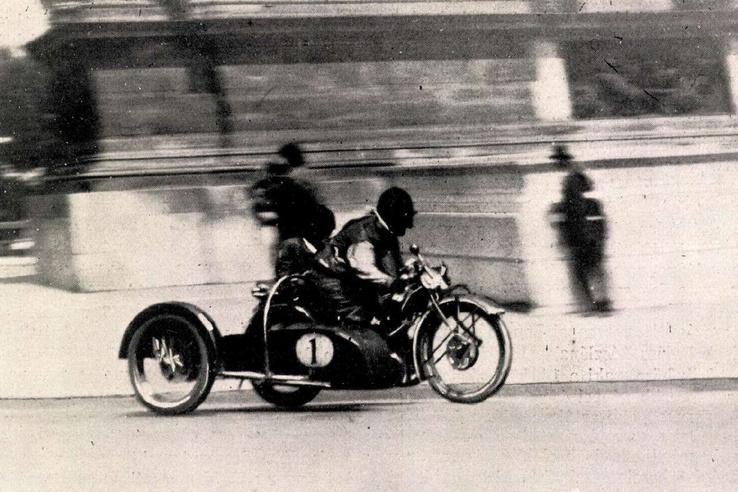 Meggyessy Zoltán (744 ohv. BMW) a milleniumi emlék melletti kanyarban. Meggyesyt csupán oldalkocsigumi                         defektje fosztotta meg a majdnem biztos győzelemtől. Forrás: Automobil - Motorsport 1929. július 28. / Arcanum adatbázis