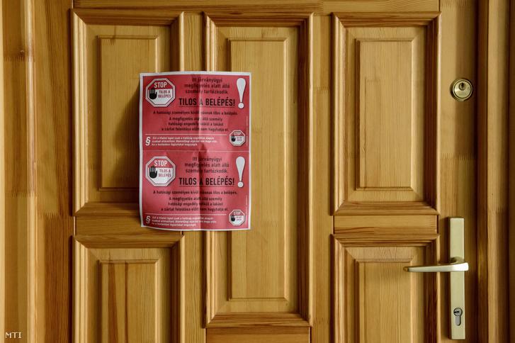 A koronavírus-járvány megfékezése érdekében hatósági felirat egy járványügyi megfigyelés alatt álló személy lakásának ajtaján