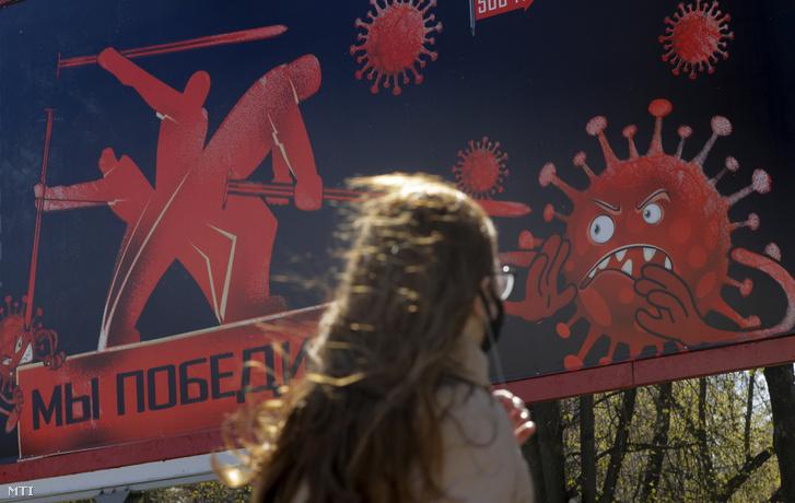 Járókelő egy koronavírust ábrázoló győzni fogunk jelentésű felirattal ellátott plakát előtt a fehérorosz fővárosban Minszkben