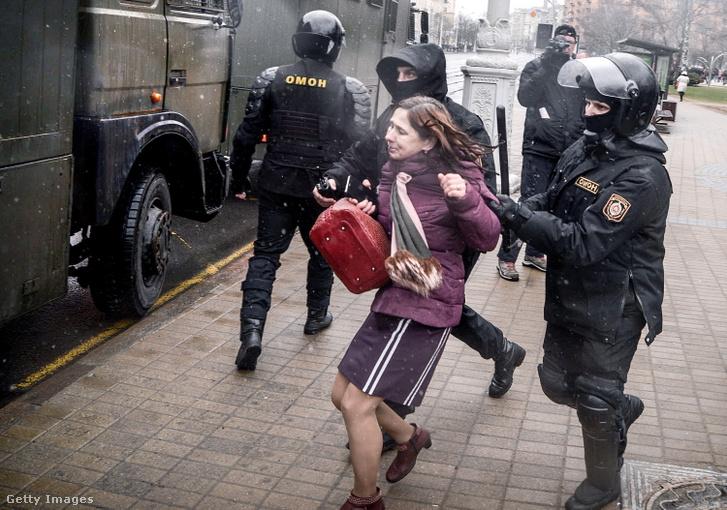 Elvezetnek egy nőt a rendőrök egy demonstráció helyszínéről Minszkben 2017-ben
