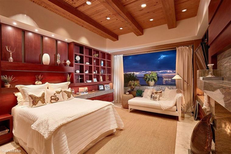 Íme, egy másik hálószoba, márványkandallóval, fabútorokkal és egy hatalmas ablakkal, kilátással az óceánra