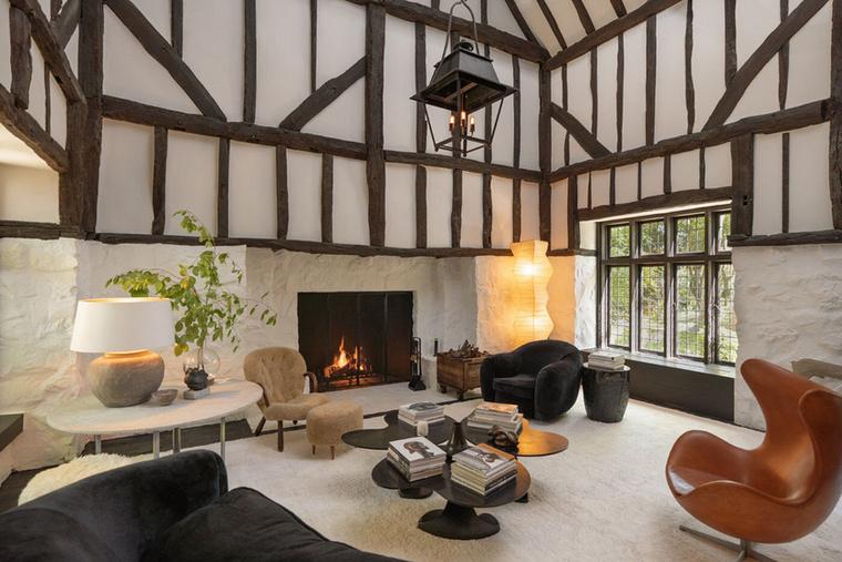 A Tudor-stílusú ház belső fehér falait sötétre pácolt gerendák díszítik, magas belmagasságának köszönhetően tágas belső terei vannak