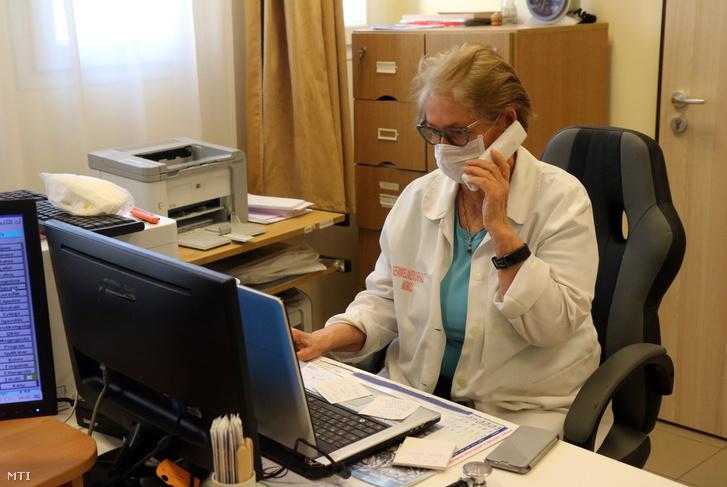 Háziorvos fogadja a betegek telefonhívását rendelőjében 2020. március 24-én.