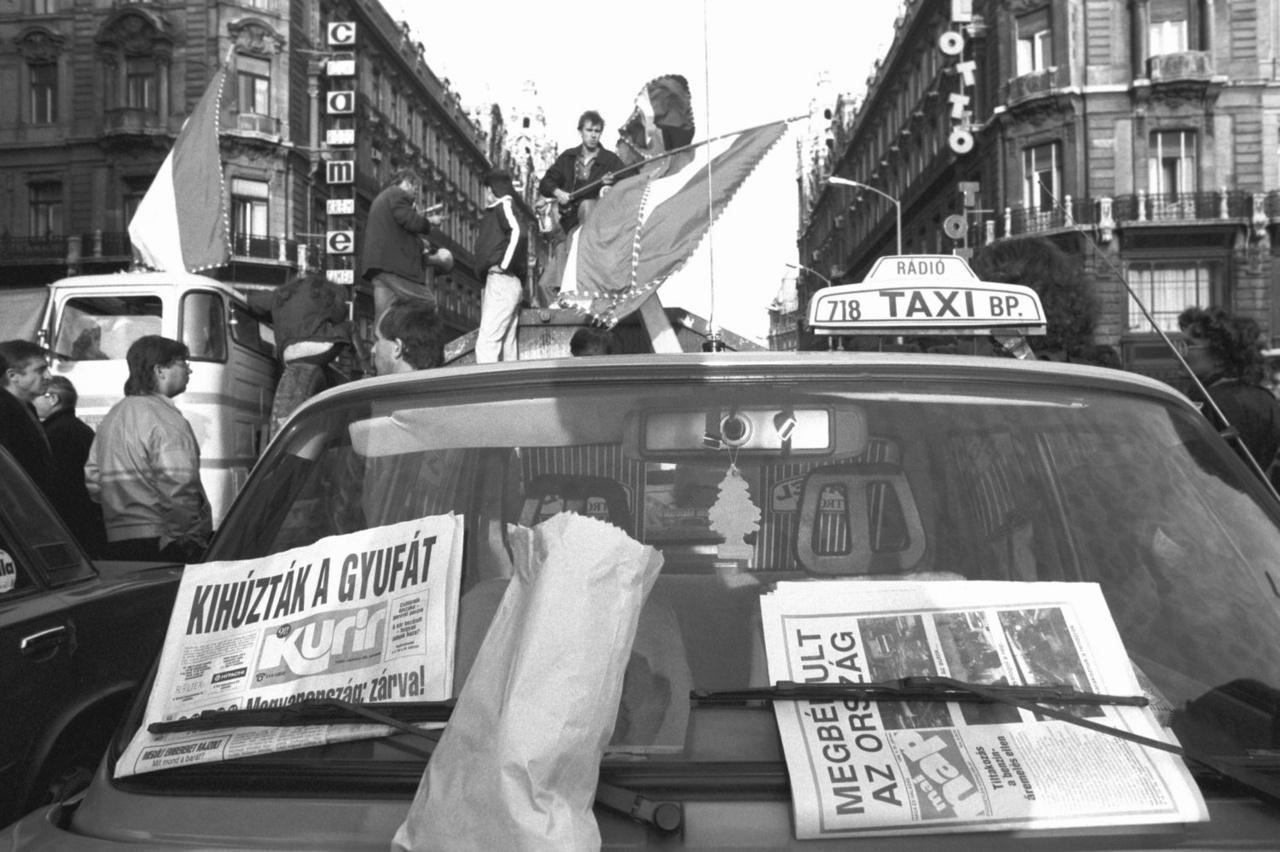 """Budapest 1990. október 26.                         A benzináremelés ellen tiltakozó taxisok demonstrálnak a lezárt Erzsébet híd pesti hídfőjénél. (MTVA Képarchívum)                                                  ___                                                  """"–Száz forint azért nem lett a benzin… És szerintem nem ez a megoldás.                         – Nem ez, persze. Hanem, hogy leengedik szépen a benzinárat. Megtanulja a Tanár úr egyszer s mindenkorra a leckét. Meg lehet egyezni a fiúkkal… ha nem is szeretik a sok pofázást…                         – Nem a pofázáson múlik – mondta János csendesen.                         – Lehet, hogy tizenöt millió magyar miniszterelnöke… de ez nem jelent tizenöt millió jótanulót… Az első nyakatekert mondata közepén, én bizony, katt, lezárom a tévét, vagy keresek valami mást. Nem bírom a szövegelését. Hallgatod, hallgatod, és nem derül ki, hogy mit akar. Hát áremelést… De akkor mért nem azt mondja?                         –Ha mondta volna – legyintett János –, akkor is lezárták volna a taxisok a hidakat.                         –Ezt nem a taxisok csinálják""""                          (Mezey Katalin: Taxisblokád vagy amit akartok)"""