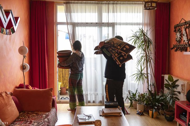 Csige Anikó és Csáki Szilárd műanyag edényeket és palántaföldet visz harmadik emeleti társasházi lakása erkélyére Nyíregyházán 2020. áprilisában. A koronavírus-járvány miatt otthon tartózkodó pár az erkélyén termeszt zöldségeket és fűszernövényeket.