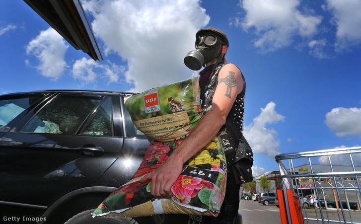 Egy gázálarcos férfi virágföldet pakol autójába egy németországi bolt parkolójában 2020 áprilisában.