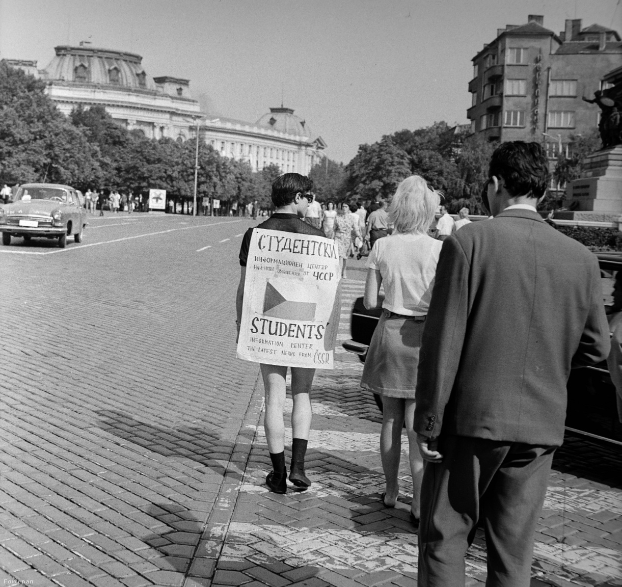 """Egyszemélyes csehszlovák információs központ, a felirat szerint a srác szívesen megmagyarázza a legfrissebb prágai híreket. A szófiai VIT-et végig beárnyékolta a csehszlovák kérdés, a brezsnyevi fenyegetés, hogy katonai erővel is visszatérítik a különutas Csehszlovákiát. A résztvevő cseh fiatalok saját reformer pártvezetésüket támogatták, ez a fiú is nyilván  Dubcekék mellett állt ki - harminc társa már el sem jutott Bulgáriába, még a határon visszafordították a hippi külsejű cseh újbalosokat, és a borotválkozás sem enyhítette meg a karhatalmat. A szerencsésebbek """"a mi demokráciánk, a mi ügyünk"""" rigmussal vonultak fel Zsivkov előtt az ünnepségen - ekkor azonban a Varsói Szerződés csapatai már bevonulásra készen,katonai készültségben álltak."""