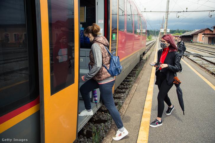 Maszkot viselő utasok szállnak fel egy vonatra Szlovéniában 2020. május 11-én