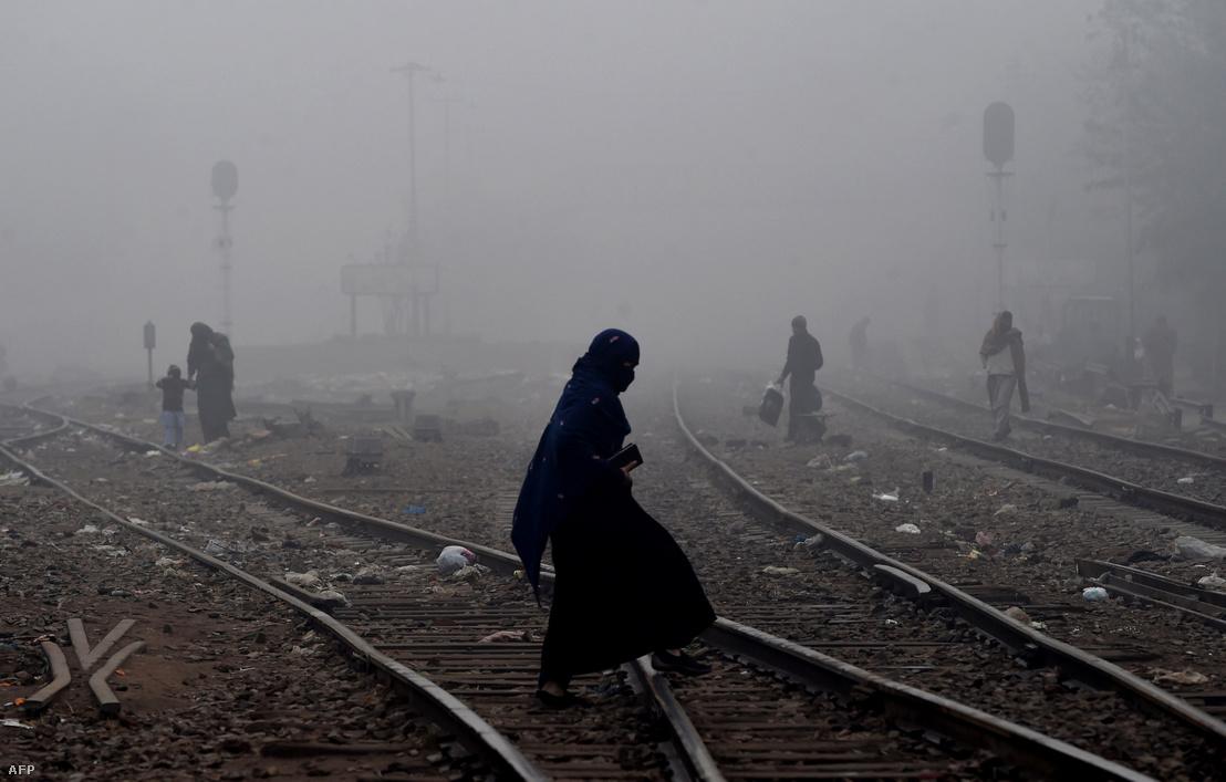 Egy pakisztáni nő sétál át egy vasútvonalon Lahore város szélén 2017. december 15-én.