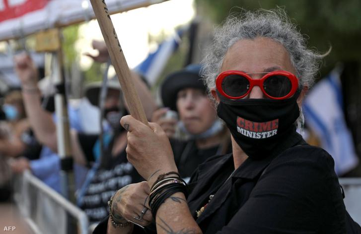 Crime Minister feliratú szájmaszkban tüntet egy tiltakozó az eskütétel alatt