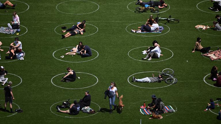A fűbe rajzolt karikákkal tartják távol egymástól az embereket egy New York-i parkban